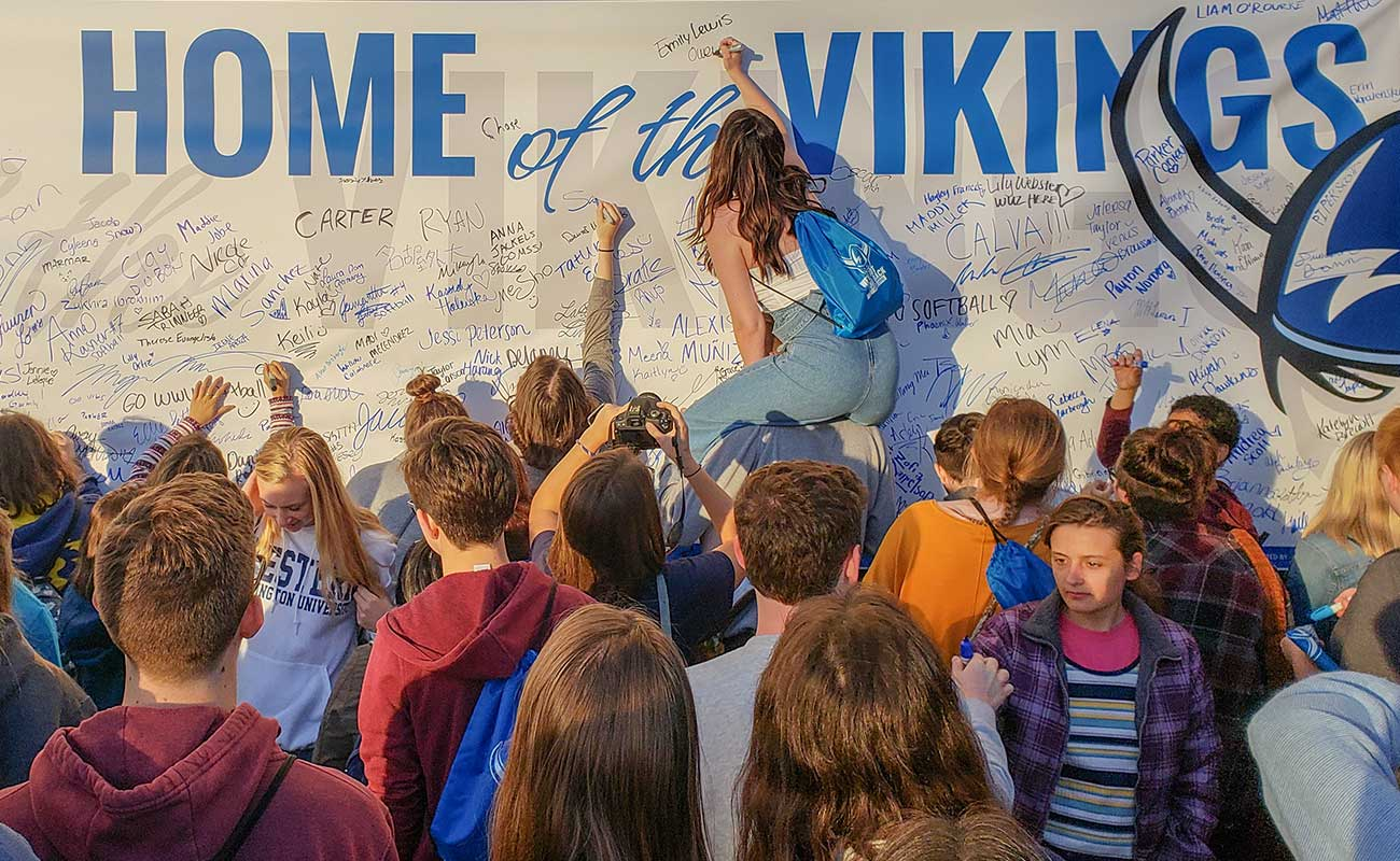 Students signing the Home of the Vikings banner during Paint B'ham Blue for WWU