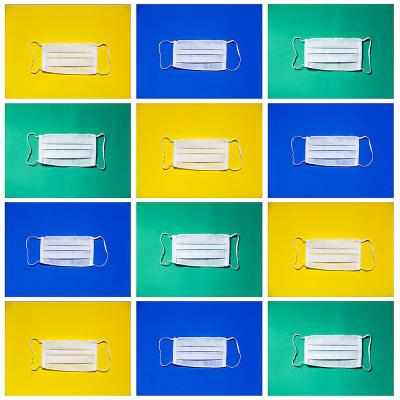 Picture of white surgical masks in a grid format. Masks are in different boxes with a yellow, blue, or green background. There are three columns and four rows of mask.  Picture also includes the Western Alumni logo in a Western blue ribbon.