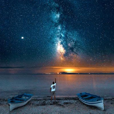 Person on the shore of a beach between two canoes at night beneath a beautiful milky way galaxy