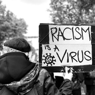Protest with a protester holding up a sign saying RACISM IS A VIRUS.