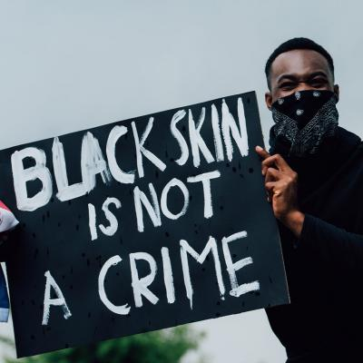 "Picture of a Black man wearing a black bandana and long, sleeved shirt holding a sign that reads ""Black skin is not a crime"". He is also holding an American flag in one hand. In the upper right corner is a WWU blue ribbon with the Alumni Association logo."