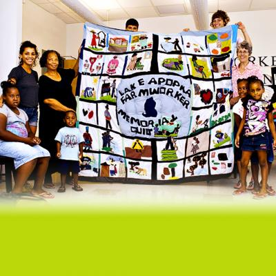 Group of children and adults holding Lake Apopka Farmworker Memorial Quilt