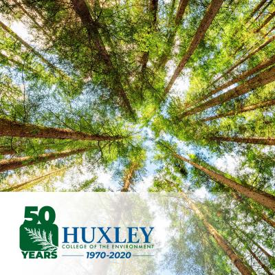 View from base of old growth trees looking up to a bright sky and Huxley 50th logo on the lower left