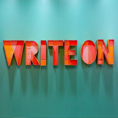 Art installation on a mint green background with giant red and orange textured block letters that read write on