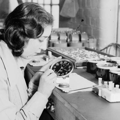 Woman painting clock face with radium
